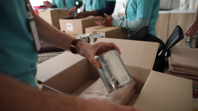 volunteers packing donation boxes in charity food bank - altruism stock videos & royalty-free footage