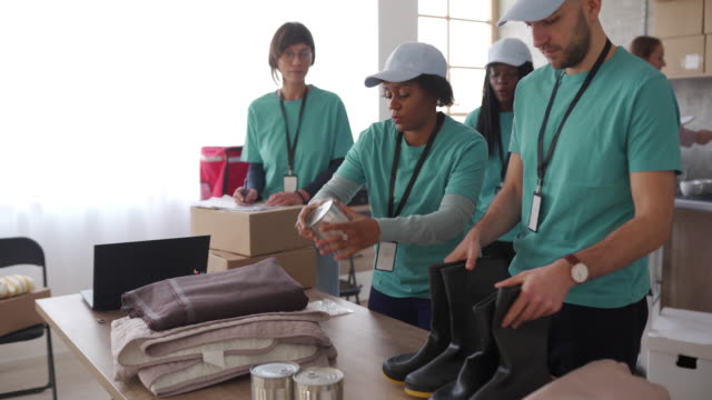 volunteers packing humanitarian aid - charitable donation stock videos & royalty-free footage