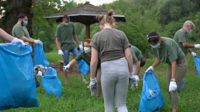 freiwillige holen müll ab, während sie während der covid-19-pandemie den öffentlichen park reinigen - gartenhandschuh stock-videos und b-roll-filmmaterial