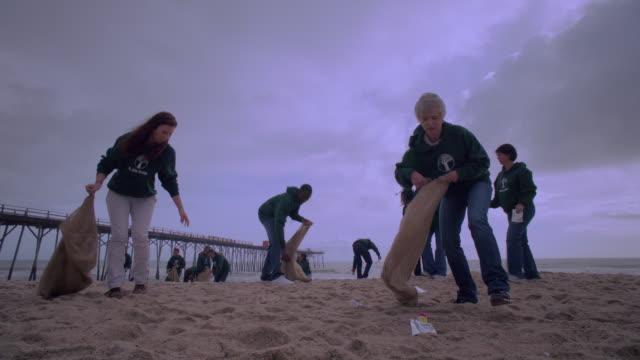 Volunteers picking up trash on beach near dock