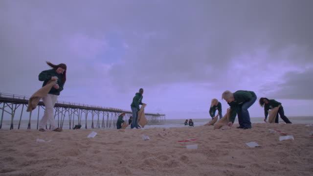 vídeos de stock e filmes b-roll de volunteers picking up trash on beach near dock - levantar