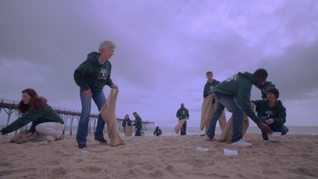 Volunteers picking up trash on beach near dock