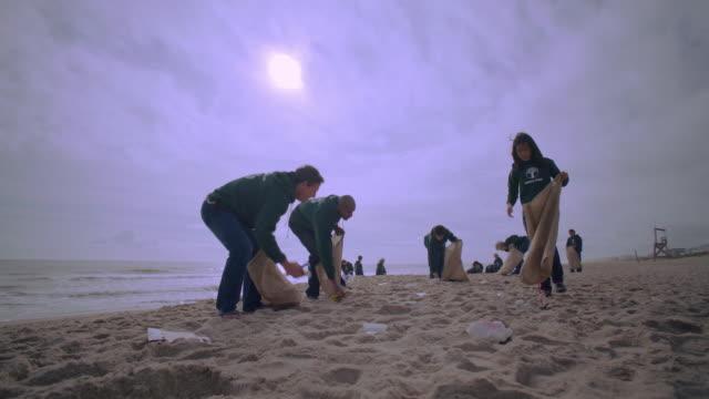 volunteers picking up trash on beach - volunteer stock videos & royalty-free footage