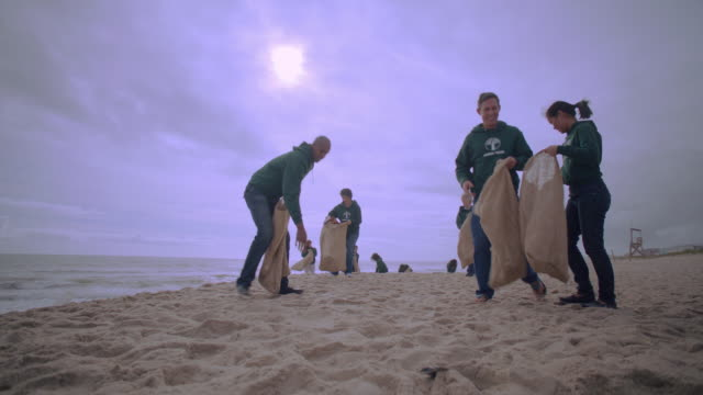 volunteers picking up trash on beach - non profit organization stock videos & royalty-free footage