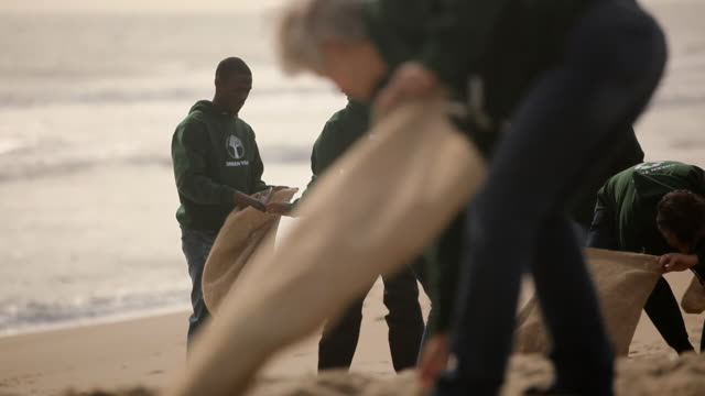 volunteers picking up trash on beach - volunteer stock videos & royalty-free footage
