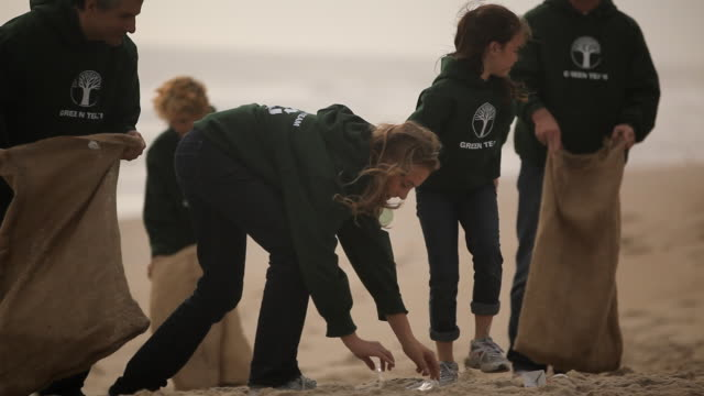 stockvideo's en b-roll-footage met volunteers picking up trash on beach - schoonmaken