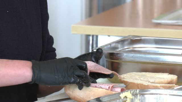 stockvideo's en b-roll-footage met volunteers prepare sandwiches for emergency food packages for distribution to the homeless in a project by the berliner stadtmission charitable... - number 9