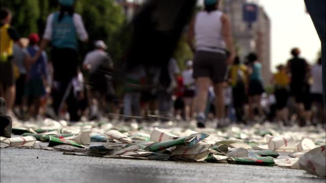 vídeos de stock e filmes b-roll de volunteers rake up used paper cups and other litter during a marathon. - ancinho equipamento de jardinagem