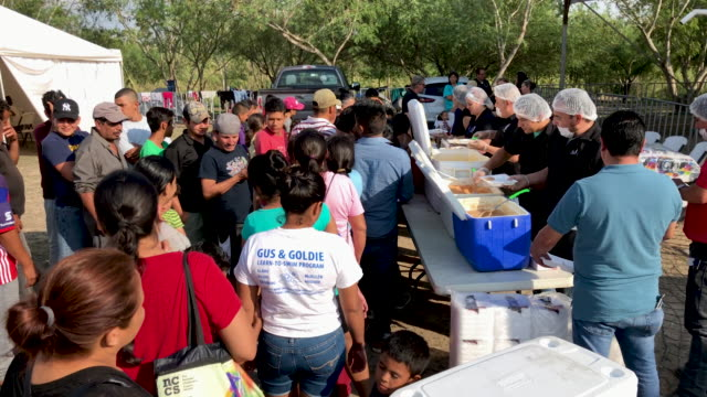 volunteers serve a meal at a camp for asylum seekers on december 08, 2019 in the mexican border town of matamoros, mexico. the squalid camp, located... - mexican american stock videos & royalty-free footage