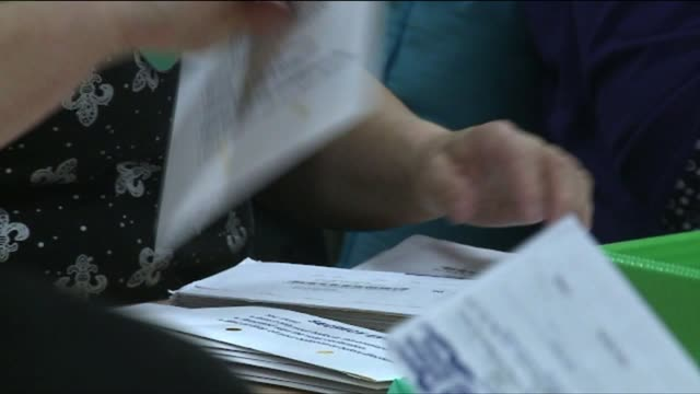 stockvideo's en b-roll-footage met volunteers sorting ballots at election center - staat washington