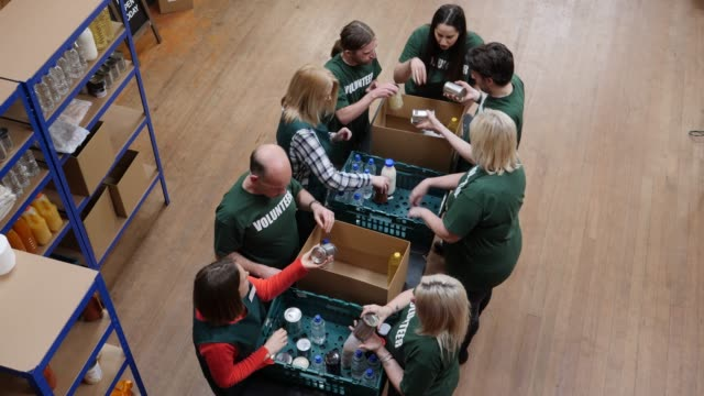 4K AERIAL: Volunteers sorting food into boxes in a Food Bank