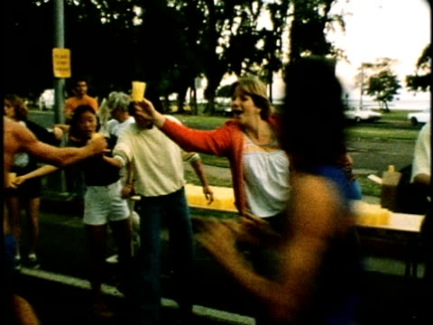 vídeos de stock e filmes b-roll de volunteers standing roadside with cups of water for passing competitors in the honolulu marathon/ marathon-winning man crossing the finish-line/... - 1976