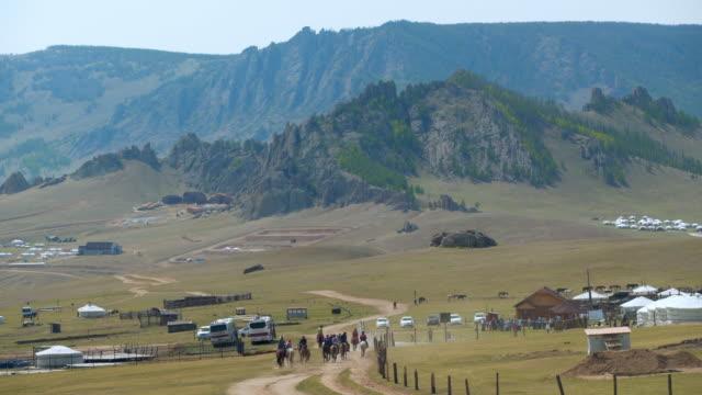 vídeos de stock e filmes b-roll de volunteers with boys horseback riding on dirt road amidst land - ulaanbaatar, mongolia - ulan bator