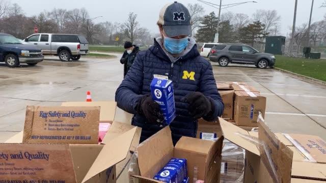 vídeos y material grabado en eventos de stock de volunteers with forgotten harvest distribute food at a mobile pantry on april 15, 2020 in oak park, michigan. the organization distributes food... - michigan