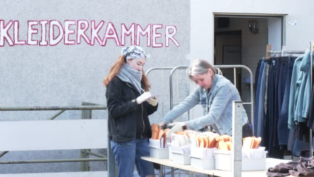 volunteers work at a distribution place to give out donated clothes for those in need at the berliner stadtmission charitable organization on april... - number 9 video stock e b–roll