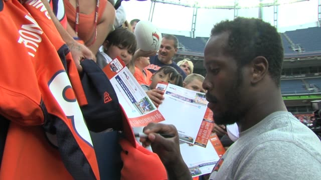 Von Miller and Peyton Manning of the Denver Broncos sign autographs before a scrimmage at Sports Authority Field Saturday August 3 2013 Von Miller...