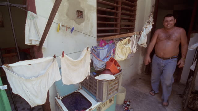 vídeos de stock, filmes e b-roll de cu, voodoo priest walking out of house, passing clothesline, havana, cuba  - só um adulto de idade mediana