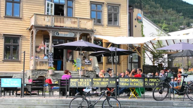 Voss Norway landmark Tre Bror Cafe wooden building with people relaxing outside in sunshine on Main Street in city