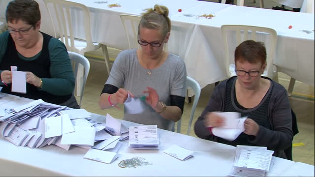 vídeos de stock, filmes e b-roll de vote counting underway in david cameron's constituency shows interior shots ballot paper being counted counting hall on may 07 2015 in witney england - título de eleitor