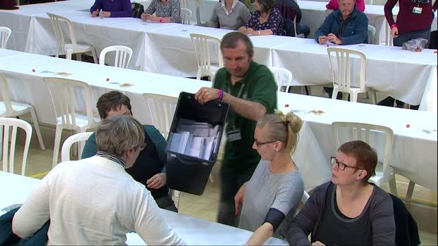 vídeos de stock, filmes e b-roll de vote counting underway in david cameron's constituency shows interior shots ballot box being emptied onto table volunteers start sorting through them... - título de eleitor