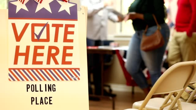 vote here. american people register to vote at polling station in usa election. - sezione elettorale video stock e b–roll