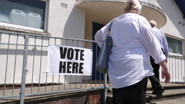 4k: vote here sign / banner - people going to vote in elections, wide shot - voting ballot stock videos and b-roll footage
