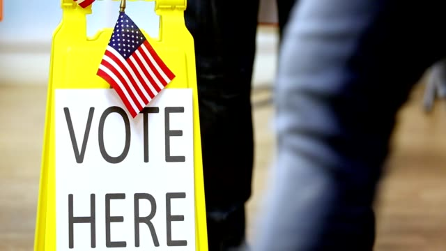 vote here sign.  people walking in, out of polling station. - stati uniti d'america video stock e b–roll