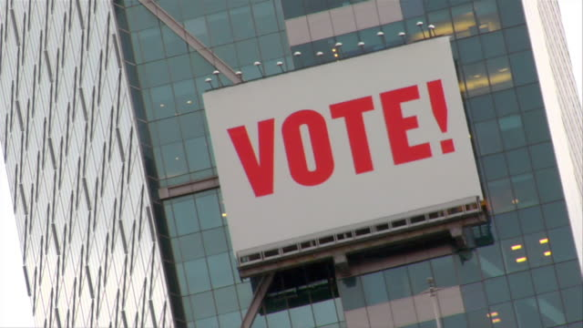 A Vote sign hangs on the front of Times Square Tower.