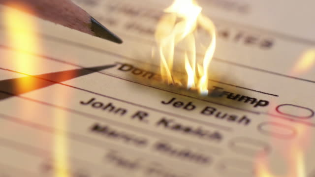a voter crosses out donald trump's name on a republican presidential primary ballot and the name is engulfed in flames - wahlschein stock-videos und b-roll-filmmaterial