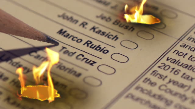a voter crosses out the name ted cruz on a republican presidential primary ballot and then the name is engulfed by flames - us republican party 2016 presidential candidate stock videos & royalty-free footage