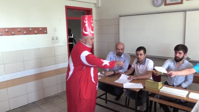 A voter dressed in the Turkish flag arrives to cast his ballot at a polling station during the parliamentary and presidential elections in...