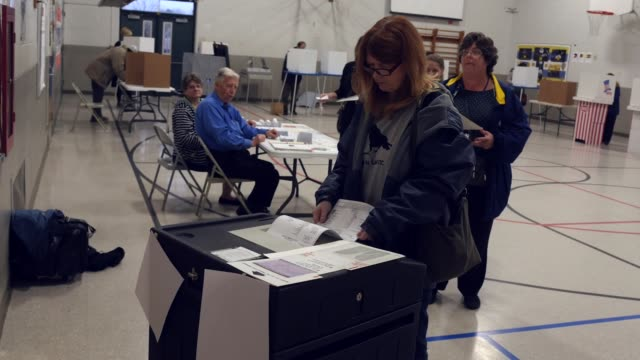 a voter has trouble inserting her ballot into an electronic scanner to be counted in the presidential election michigan voters gave donald trump a... - vallokal bildbanksvideor och videomaterial från bakom kulisserna