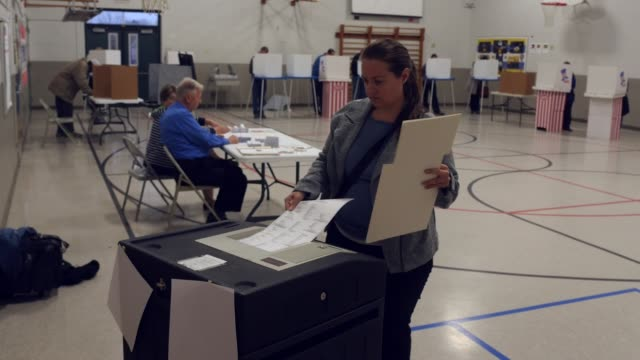 vídeos de stock e filmes b-roll de a voter has trouble inserting her ballot into an electronic scanner to be counted in the presidential election michigan voters gave donald trump a... - boletim de voto