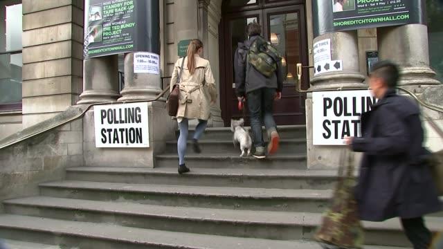 vídeos y material grabado en eventos de stock de voter id trial to crack down on electoral fraud; t07051531 / tx 7.5.2015 england: london : shoreditch: ext man and woman arriving at polling station... - fraude