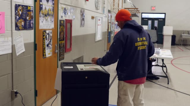 A voter inserts his ballot into an electronic scanner to be counted in the presidential election Michigan voters gave Donald Trump a narrow...