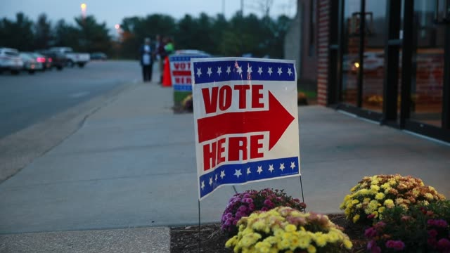 vídeos de stock, filmes e b-roll de a voter passes a sign that points voters to the polling site at sherwood oaks christian church in bloomington indiana on election day 2016 the... - bloomington indiana