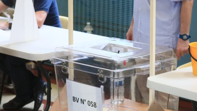 vidéos et rushes de voter places ballot in ballot box in a polling station in the 15th arrondissement of paris during the second round of mayoral elections on june 28... - isore vincent