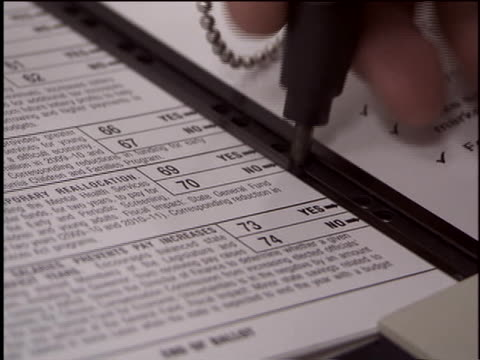 voter uses a punch card ballot to cast her votes. - wahlschein stock-videos und b-roll-filmmaterial