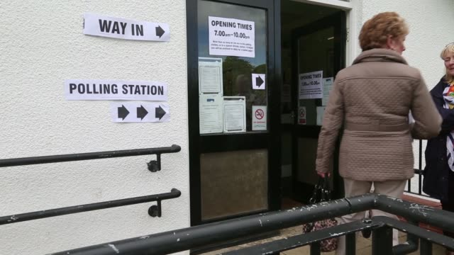 voters enter a polling station to cast their votes in the general election in hull uk on thursday may 7 2015 shots polling station signage - allgemeine wahlen stock-videos und b-roll-filmmaterial