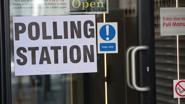 Voters enter a polling station to cast their votes in the general election in London UK on Thursday May 7 2015 SHOTS polling station signage