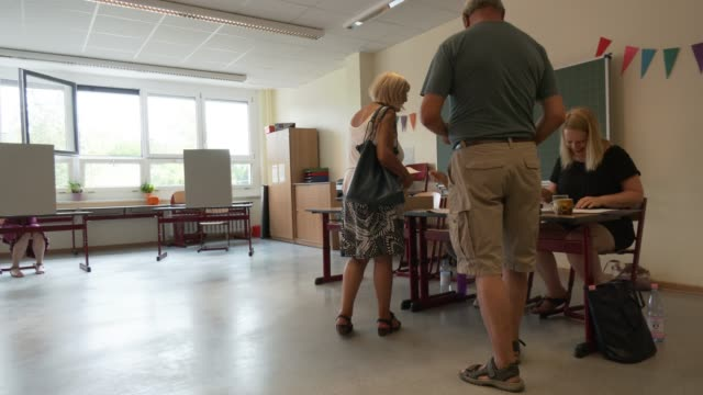 vídeos de stock, filmes e b-roll de voters fill in their ballots at a polling station on september 1 2019 in potsdam germany - primary election