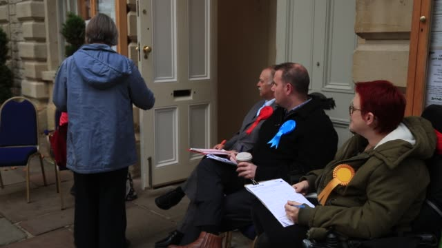 stockvideo's en b-roll-footage met voters pass party tellers outside the polling station inside the corn exchange on october 20 2016 in witney england the byelection in witney... - mp