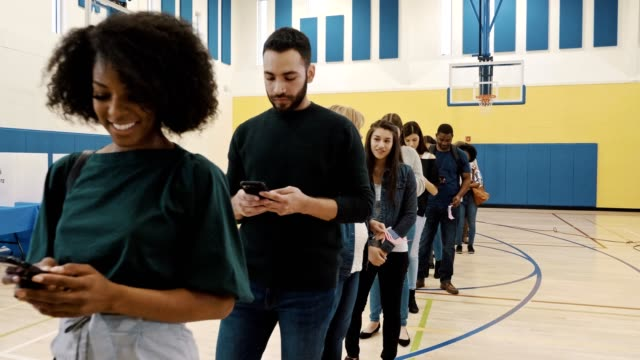 voters use smartphones while waiting in line to vote - fare la fila video stock e b–roll
