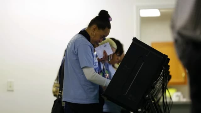 stockvideo's en b-roll-footage met voters use the voting machines to cast their ballots on election day greensboro nc november 4 2014 - tussentijdse verkiezing