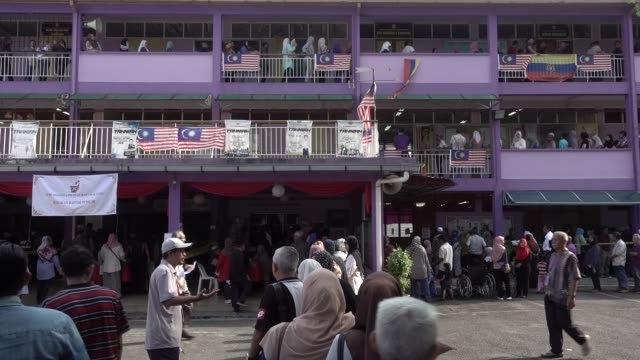 voters wait in line at a polling station in kampung baru for the 14th general election on may 9 2018 in kuala lumpur malaysia millions of malaysians... - general election stock videos & royalty-free footage
