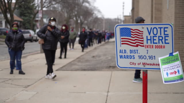 voters waiting in line and a worker sanitizing the door at a polling location for the presidential primary at washington high school in milwaukee... - wisconsin stock videos & royalty-free footage