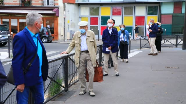 voters wearing surgical masks wait while respecting physical distance at a polling station in the 15th arrondissement of paris during the second... - french culture stock videos & royalty-free footage