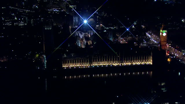 vídeos de stock, filmes e b-roll de votes counted across the country after a day of people going to the polls shows exterior aerial night shots westminster palace lit up pan around big... - título de eleitor