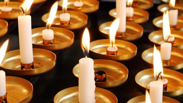 votivkerzen brennen in einer kirche - kerzenschein stock-videos und b-roll-filmmaterial