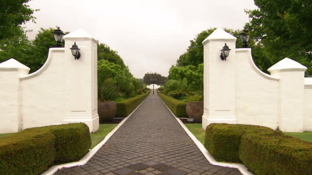 Voyager Estate Winery Garden Entrance way white rendered brick fence with black coach lights view down paved pathway leads down a beautifully...